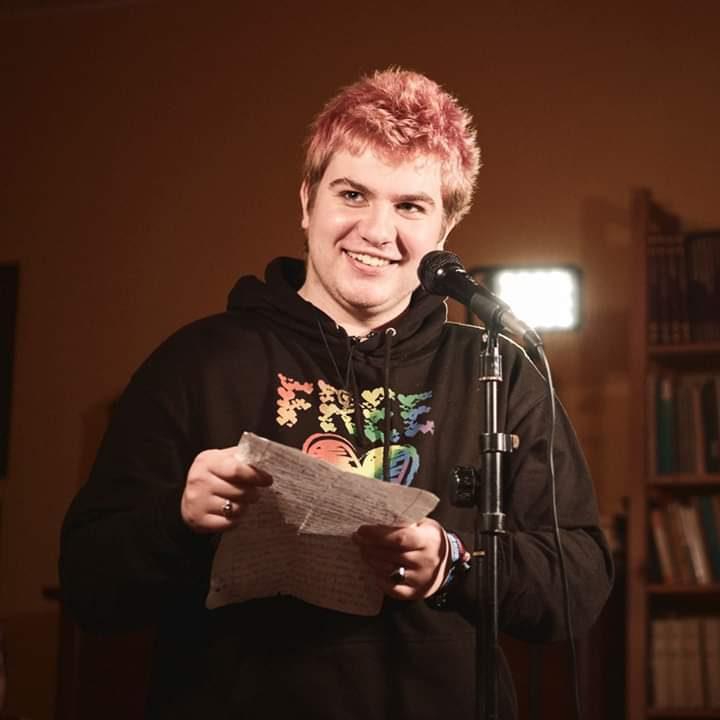 Locke lächelt beim Lesen am Mikro