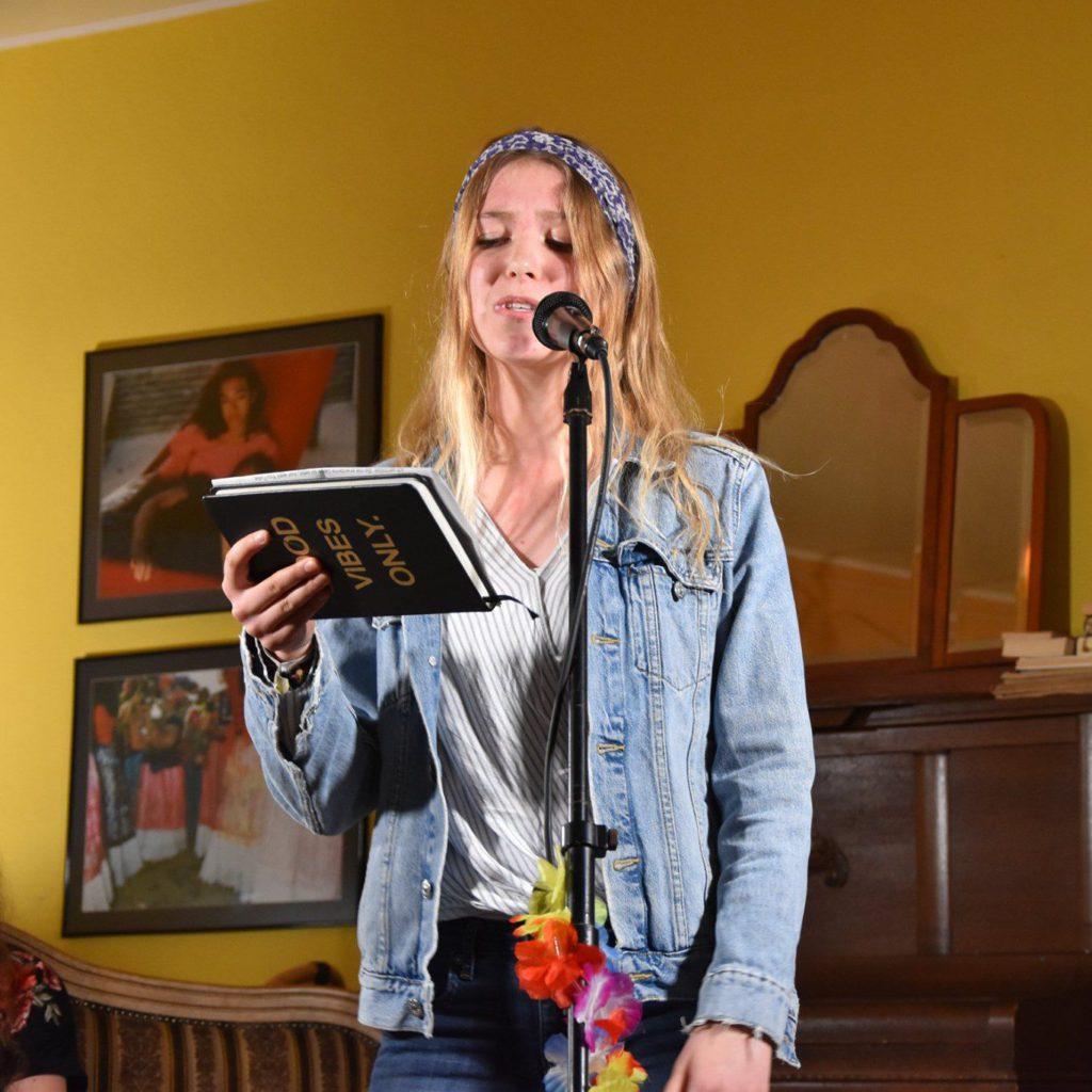 """Amelie Werner liest am Mikro, auf ihrem Notizbuch steht """"GOOD VIBES ONLY"""""""