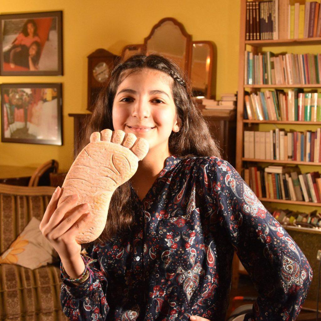 Lavin lächelt, hält einen Fuß aus Gips in der Hand. Sofa und Bücherwand im Hintergrund.