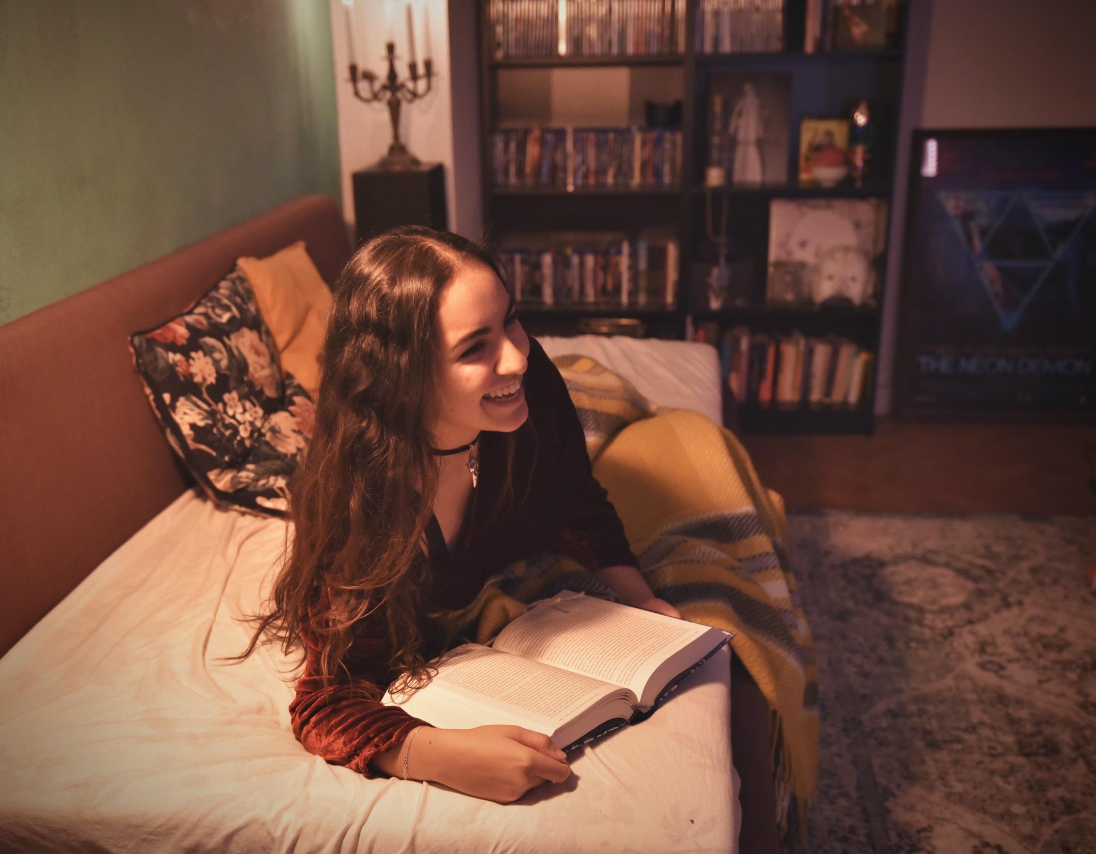 Yasmin liegt lachend und lesend auf ihrer Couch